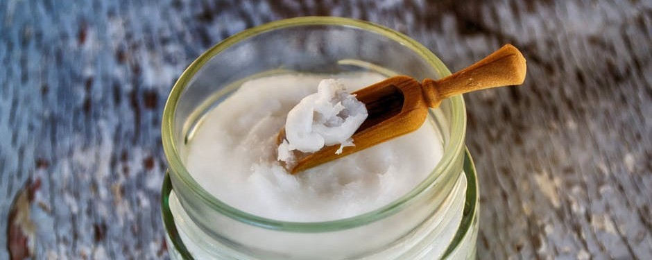 Coconut oil in glass jar with scoop